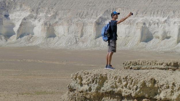 Een jonge reiziger staat op de rand van een klif en maakt een selfie Premium Foto