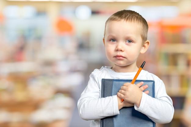 Een jonge schooljongen houdt een blauw boek Premium Foto