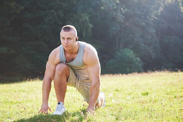 Een jonge sportman die zich klaarmaakt voor atletiek- en fitnesstraining buitenshuis. Gratis Foto