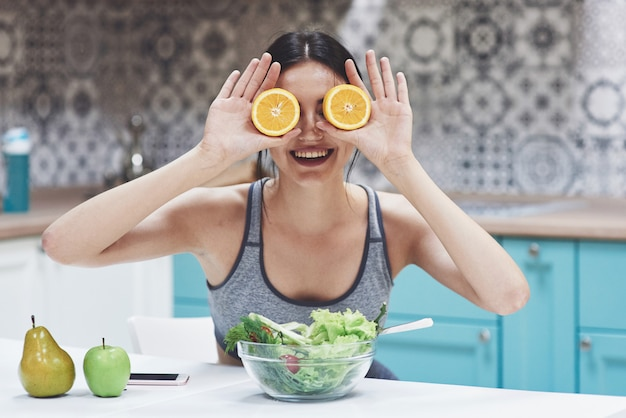 Een jonge sportvrouw geniet van een fruitsalade. speels zijn en haar ogen bedekken met oranje Premium Foto