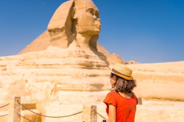 Een jonge toerist bij de grote sfinx van gizeh, gekleed in het rood en met een hoed, vanwaar de miramides van gizeh. caïro, egypte Premium Foto