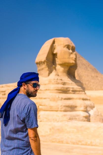 Een jonge toerist die de grote sfinx van gizeh geniet en bewondert, gekleed in blauw en een blauwe tulband. caïro, egypte Premium Foto