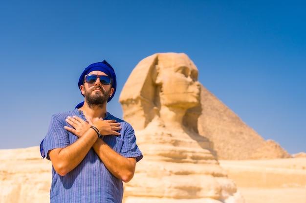 Een jonge toerist in de buurt van de grote sfinx van gizeh, gekleed in blauw en een blauwe tulband, vanwaar de miramides van gizeh. caïro, egypte Premium Foto