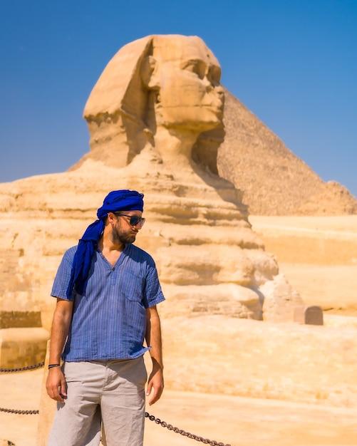 Een jonge toerist in de buurt van de grote sfinx van gizeh gekleed in het blauw en een blauwe tulband, van waaruit de miramides van gizeh, cultureel toerisme en veel geschiedenis. caïro, egypte Premium Foto