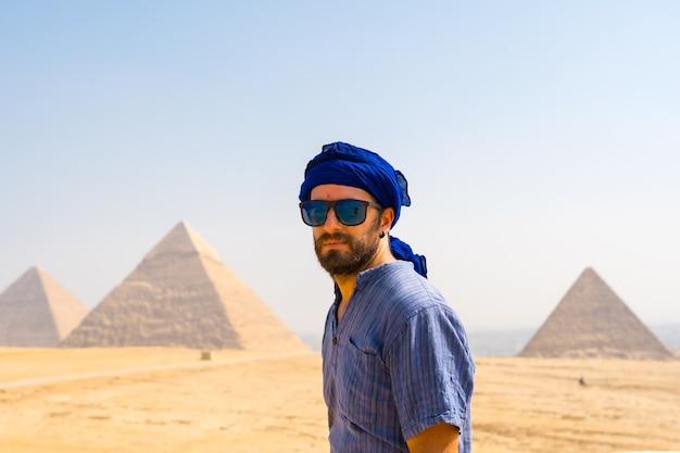 Een jonge toerist met een blauwe tulband en een zonnebril genietend van de piramides van gizeh, het oudste grafmonument ter wereld. in de stad caïro, egypte Premium Foto