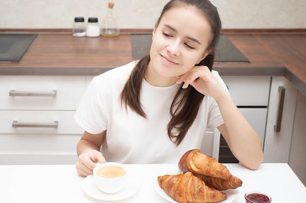 Een jonge vrouw aan een tafel in de keuken aan het ontbijt, glimlachen, praten, verse croissants eten. is koffie aan het drinken Premium Foto