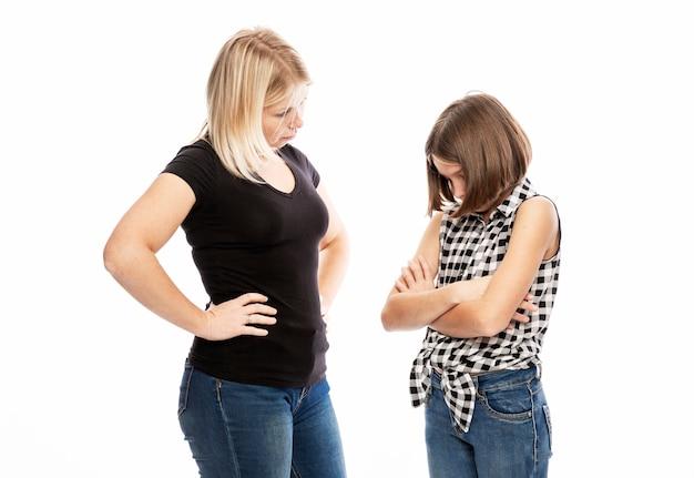 Een jonge vrouw berispt de dochter van een tiener. het conflict van generaties. witte muur. Premium Foto