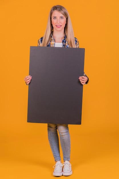 Een jonge vrouw die leeg zwart aanplakbiljet in de hand houden tegen een oranje achtergrond Gratis Foto
