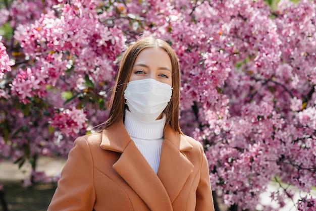 Een jonge vrouw doet haar masker af en haalt diep adem na het einde van de pandemie op een zonnige lentedag Premium Foto