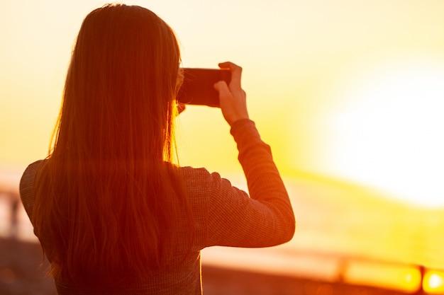 Een jonge vrouw fotografeert de zonsondergang op het strand. Premium Foto