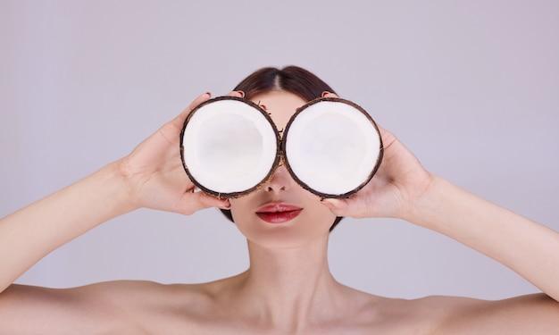 Een jonge vrouw houdt kokosnoten in haar handen als een bril. Premium Foto
