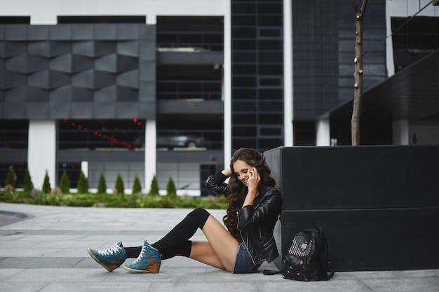 Een jonge vrouw in denim shorts en leren jas praten via de telefoon en zittend op de straat van een europese stad op een zomerse dag Premium Foto