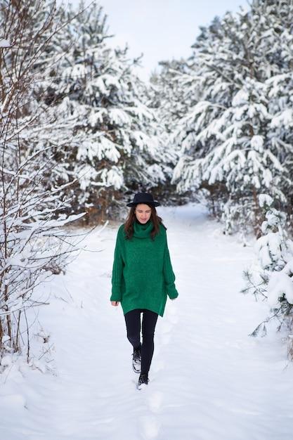 Een jonge vrouw in een donkergroene trui en hoed staat midden in een prachtig winterbos Premium Foto