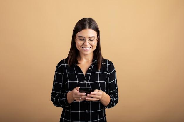 Een jonge vrouw in een geruite jurk staat op een oranje achtergrond en speelt met haar telefoon Premium Foto