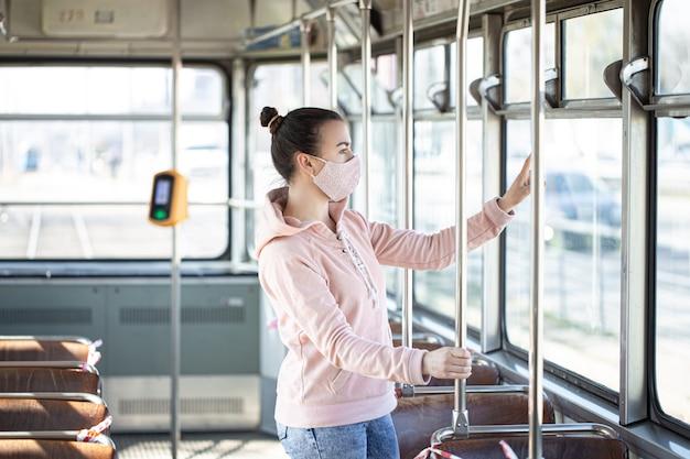 Een jonge vrouw in een leeg openbaar vervoer tijdens de pandemie. coronavirus. Gratis Foto
