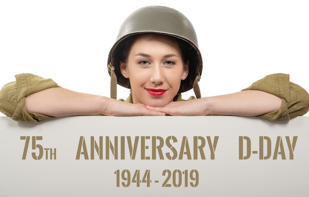 Een jonge vrouw kleedde zich in ons wwii militair uniform met helm die uithangbord toont Premium Foto