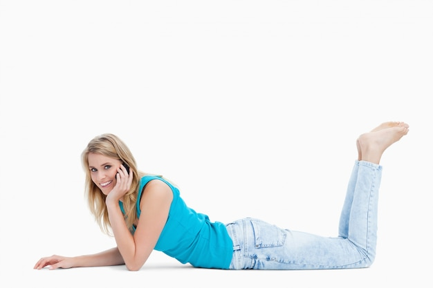 Een jonge vrouw lacht naar de camera en praat met haar mobiele telefoon Premium Foto