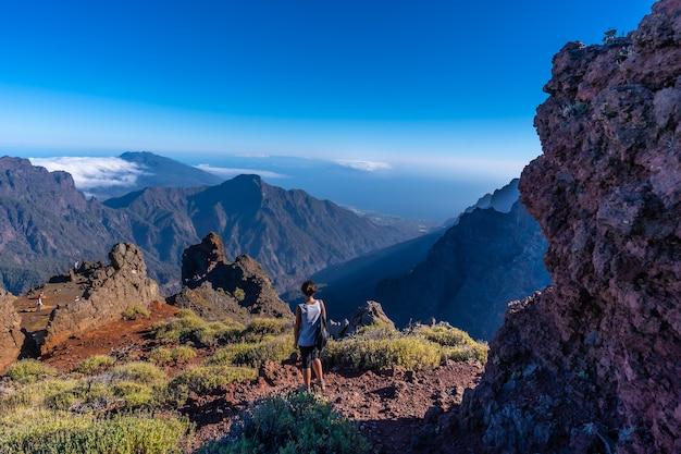 Een jonge vrouw loopt in een natuurlijk uitzichtpunt van de caldera de taburiente tijdens de trektocht nabij roque de los muchachos op een zomermiddag, la palma, canarische eilanden. spanje Premium Foto