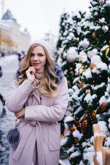 Een jonge vrouw loopt met kerstmis op het plein bij de versierde kerstbomen. candy is een lolly in de vorm van een hart. Premium Foto