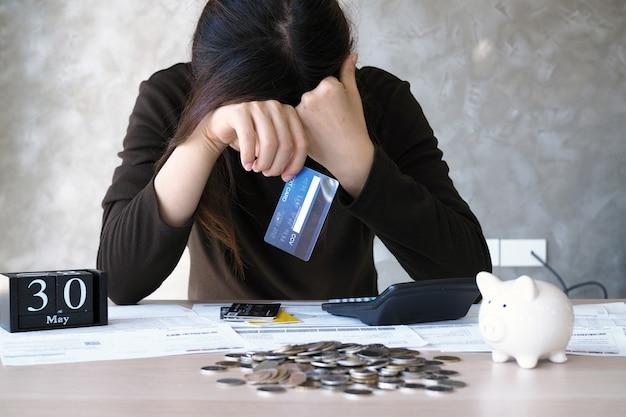 Een jonge vrouw met een creditcardschuld en veel rekeningen op de tafel. Premium Foto