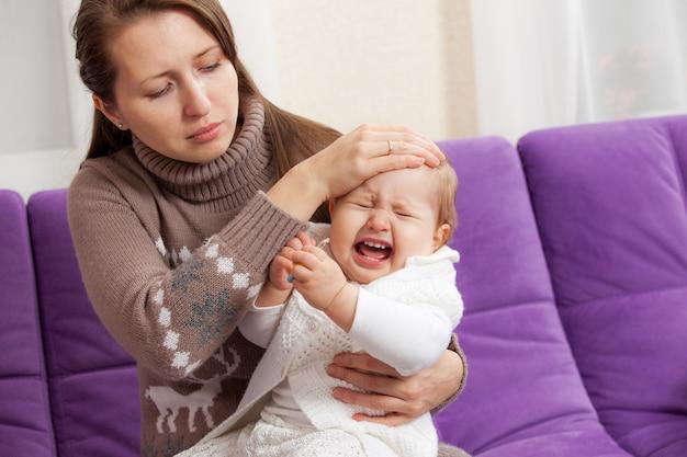 Een jonge vrouw met een zieke huilende baby Premium Foto