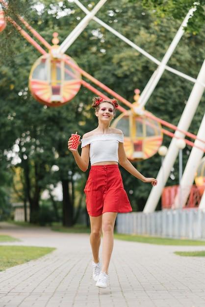 Een jonge vrouw met lichte make-up houdt een rode papieren beker in haar handen en rent door een pretpark. ze glimlacht en gelukkig. Premium Foto