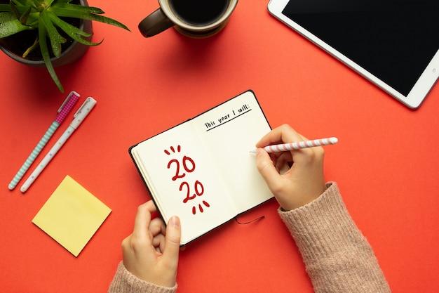 Een jonge vrouw overhandigt het schrijven in een 2020 nieuwjaarsnotitieboekje met lijst van doelen en objecten op rode achtergrond Premium Foto