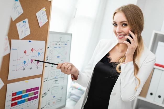 Een jonge vrouw staat bij het bord met stickers, praat aan de telefoon en houdt een potlood in haar hand. Premium Foto