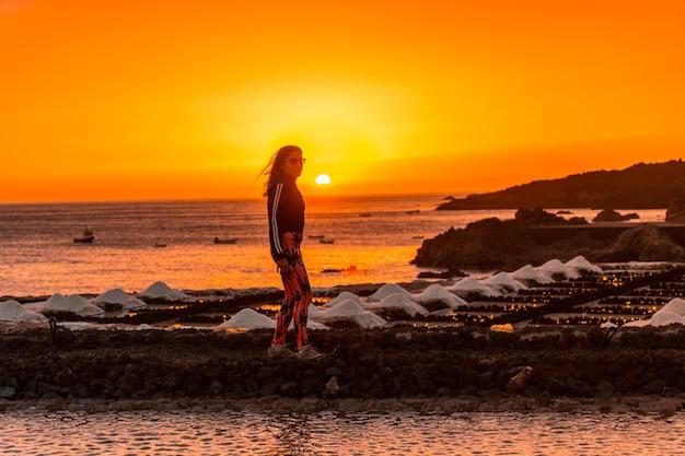 Een jonge vrouw wandelen in de oranje zonsondergang in de salina en op de achtergrond de fuencaliente-vuurtoren op de route van de vulkanen ten zuiden van het eiland la palma, canarische eilanden, spanje Premium Foto