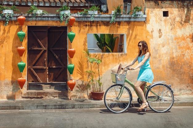 Een jonge vrouwentoerist in een blauwe korte jurk rijdt op een fiets langs de straat van de vietnamese toeristenstad hoi an. fietsen door de oude stad hoi an. Premium Foto