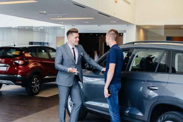 Een jonge zakenman met een verkoper kijkt naar een nieuwe auto in een autodealer. een auto kopen. Premium Foto