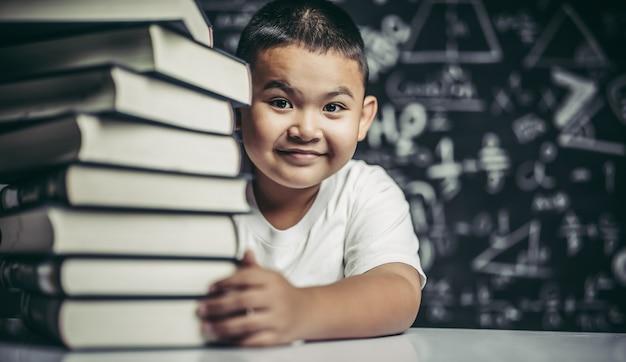 Een jongen die een stapel boeken koestert. Gratis Foto