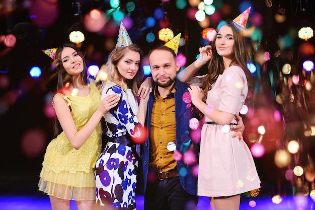 Een jongen en drie meisjes zijn blij en vieren het feest in de nachtclub Premium Foto