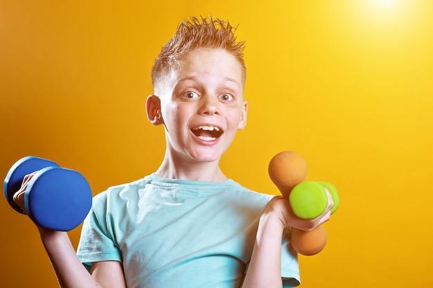 Een jongen in een fel t-shirt met halters op een geel Premium Foto