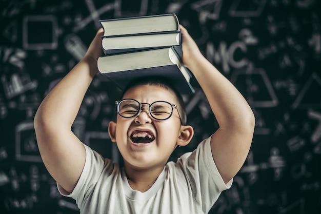 Een jongen met bril studeerde en legde een boek op zijn hoofd in de klas. Gratis Foto