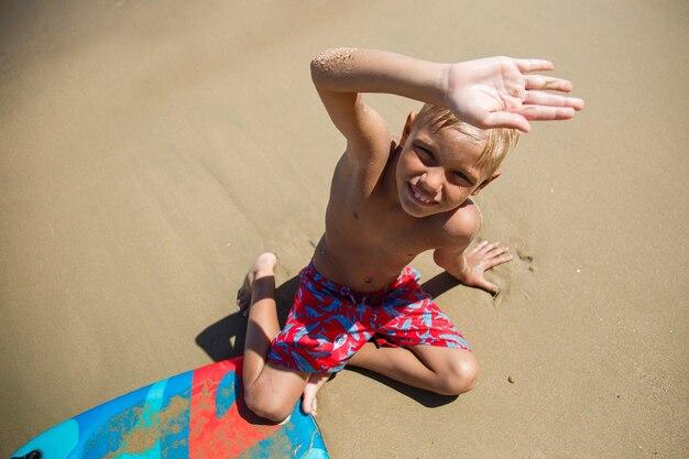 Een jongen met een bodyboard op een golf Premium Foto