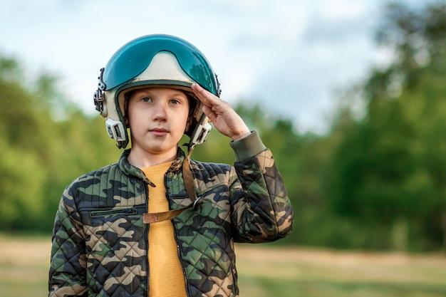 Een jongen met een pilotenhelm salueert. Premium Foto