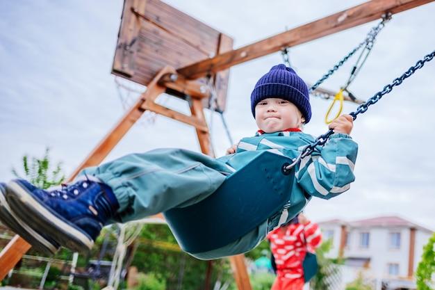 Een jongen met het syndroom van down speelt op de speelplaats, hij schommelt op een schommel. genetische ziekte bij een kind. selectieve aandacht Premium Foto