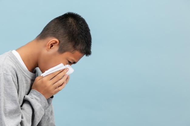 Een jongen niest in weefsel en voelt zich ziek op de blauwe muur. Gratis Foto
