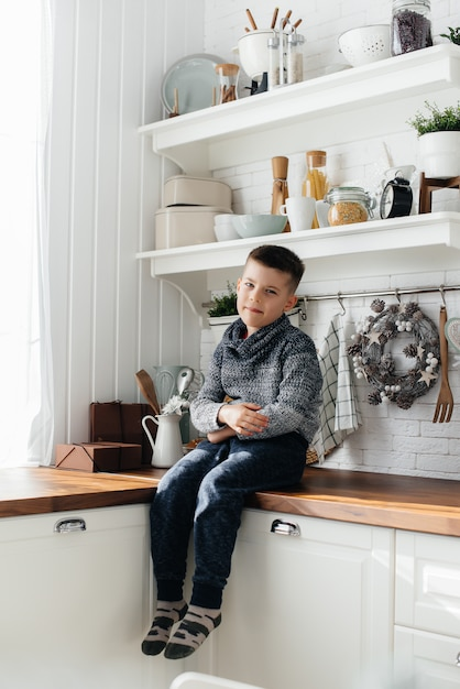 Een jongen speelt en ontbijt in de keuken. geluk. een familie. Premium Foto