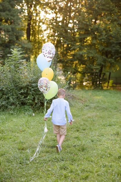 Een jongen van de basisschoolleeftijd rent met ballonnen. de jongen wijst met zijn rug naar de camera. Premium Foto