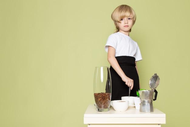 Een jongen van het vooraanzichtblonde in witte t-shirt dichtbij lijst die koffie op de steen gekleurde ruimte voorbereiden Gratis Foto