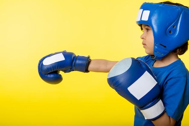 Een jongen van het vooraanzichtkind in blauwe handschoenen en blauwhelm het in dozen doen op de gele muur Gratis Foto