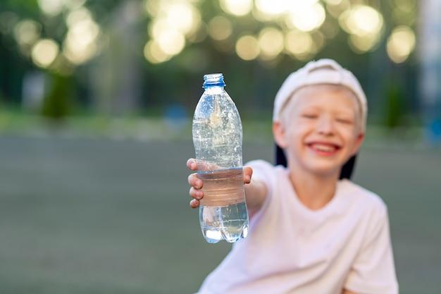 Een jongen zit op een groen gazon op een voetbalveld en houdt een fles water vast. focus op de waterfles Premium Foto