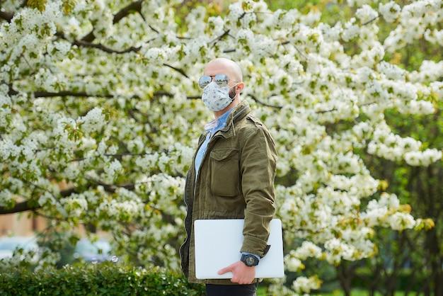 Een kale man met een baard in een medisch gezichtsmasker om de verspreiding van het coronavirus te vermijden, loopt met een laptop in het park. een man draagt een gezichtsmasker n95 en een pilotenzonnebril in de tuin tussen bloeiende bomen. Premium Foto