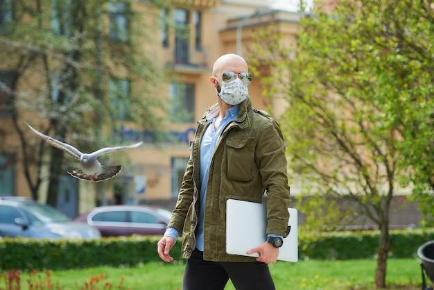 Een kale man met een baard in een medisch gezichtsmasker om de verspreiding van het coronavirus te vermijden, loopt met een laptop in het park. een man draagt een gezichtsmasker n95 en een pilotenzonnebril op straat bij een vliegende duif. Premium Foto