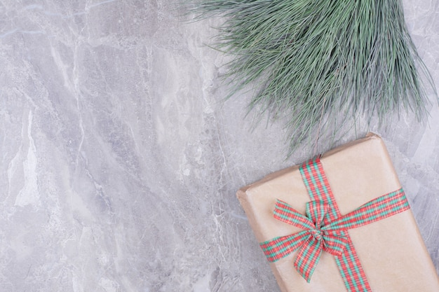 Een kartonnen geschenkdoos omwikkeld met lint en kruiden Gratis Foto