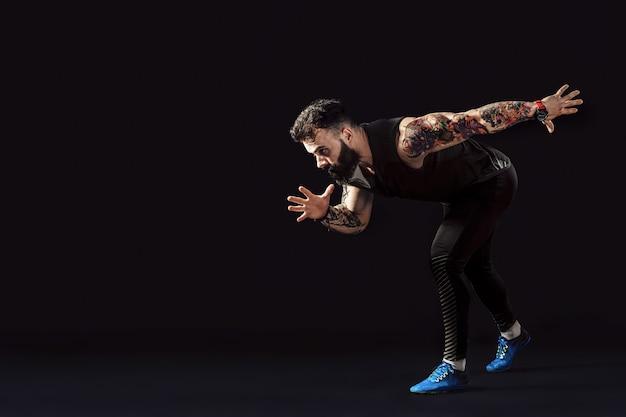 Één kaukasische agent die van de mensen jonge sprinter in silhouetstudio lopen op donkere achtergrond. Premium Foto