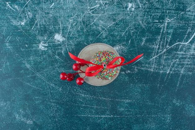 Een kerstbes ornament en een lolly op een stuk hout op blauwe achtergrond. hoge kwaliteit foto Gratis Foto