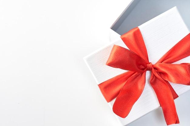 Een kerstcadeau in wit inpakpapier en rode linten Premium Foto